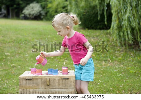 little girl playing tea party in the garden - stock photo