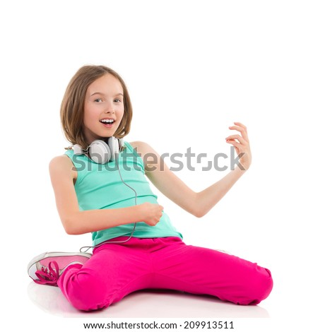 Little girl playing the air guitar and singing. Full length studio shot isolated on white. - stock photo