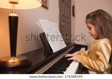 Little girl playing the piano with notes - stock photo