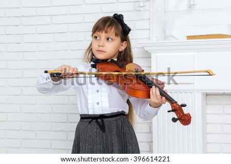 little girl playing the violin and looking away