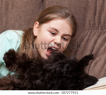 Little girl playing to her dog - stock photo