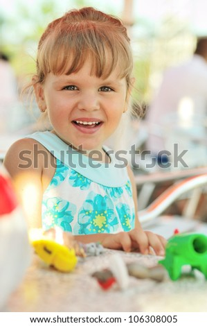 little girl playing toys and smiling
