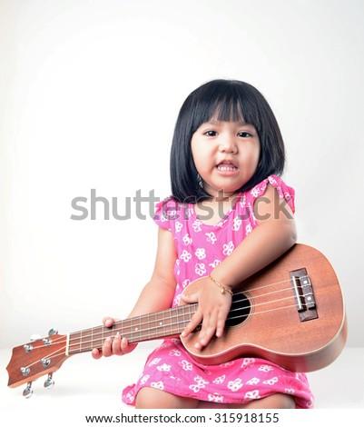 Little girl playing ukulele  - stock photo