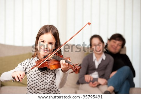 little girl playing violin with her family at home - stock photo