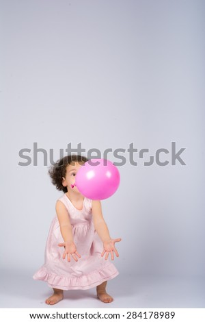 little girl playing with a balloon
