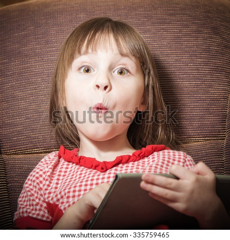 Little girl playing with a modern digital tablet in a room. - stock photo