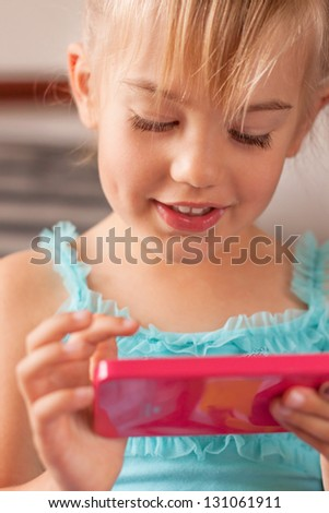 Little girl playing with a smartphone - stock photo