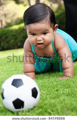 Little girl playing with a soccer ball in a park