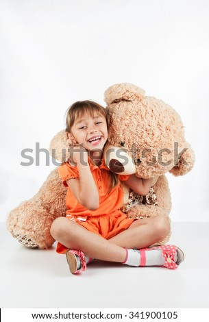 Little girl playing with a teddy bear, on a white background