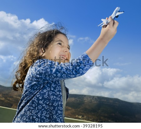 little girl playing with a toy airplane against cloudy blue sky