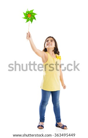 Little girl playing with a toy windmill - stock photo