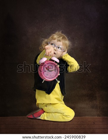 little girl playing with an alarm clock - stock photo