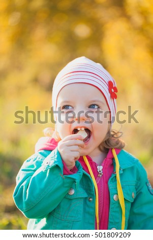 Little girl playing with autumn leaves in the park. Little girl in a red cap