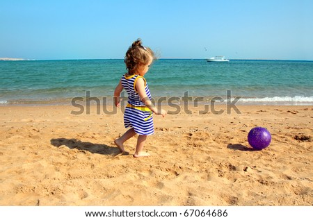 little girl playing with ball on beach - stock photo