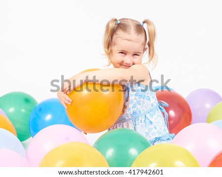 Little girl playing with balloons.Happy little girl holding balloon.Smiling kid. Isolated on white background. - stock photo
