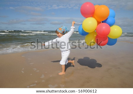 Little girl playing with balloons on the beach