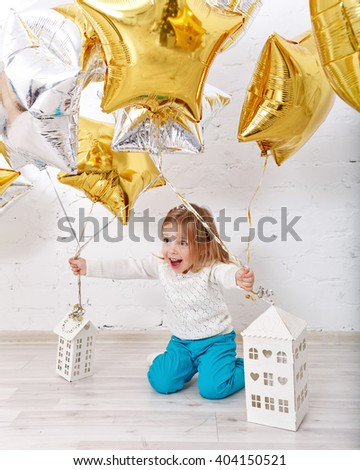 Little girl playing with balloons. The atmosphere of joy, fun, holiday. Birthday. - stock photo