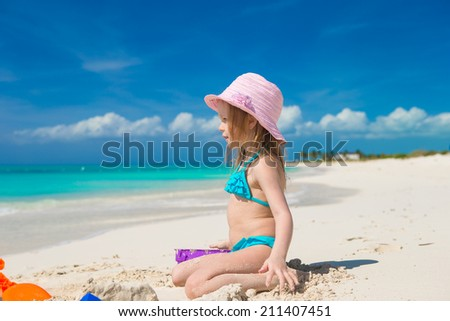 Little girl playing with beach toys during carribean vacation