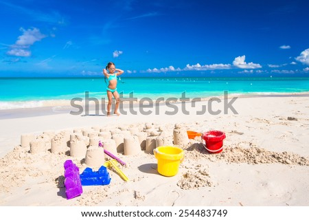 Little girl playing with beach toys during tropical vacation - stock photo