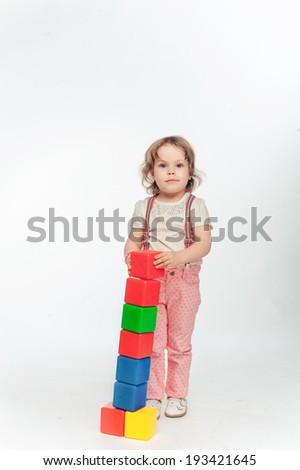 Little girl playing with blocks and builds a tower