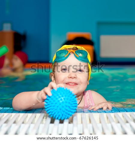 Little girl playing with blue ball in a swimming pool - stock photo