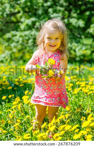 Little girl playing with bouquet in the park