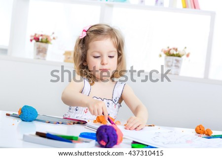 little girl playing with colored plasticine and drawing with crayons on the album. child having fun at home.