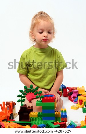 Little girl playing with colorful cube blocks