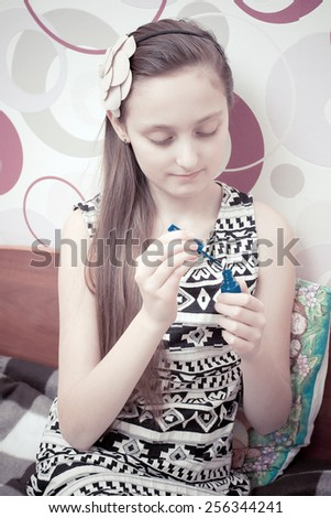 Little girl playing with cosmetics of her mother at home - stock photo
