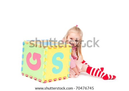 Little girl playing with cube - stock photo