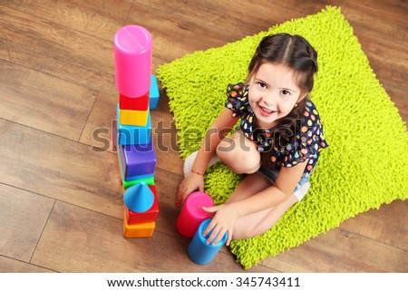 Little girl playing with cubes on home interior background - stock photo