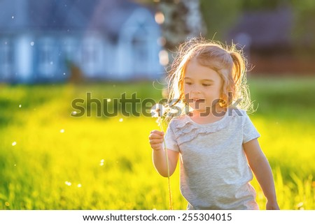 Little girl playing with dandelions in sunny park - stock photo