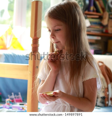 Little girl playing with dolls and toy dishes for tea in the children