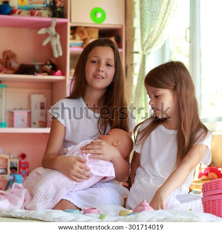 Little girl playing with dolls and toy dishes for tea in the children - stock photo