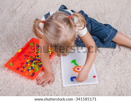 little girl playing with education mosaic pins toy - stock photo
