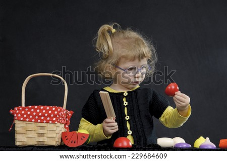 little girl playing with fake fruit, on dark background - stock photo