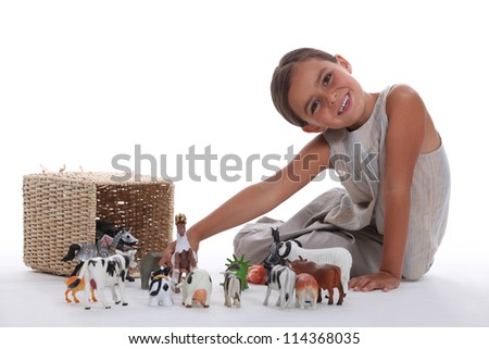 Little girl playing with farm animal toys - stock photo
