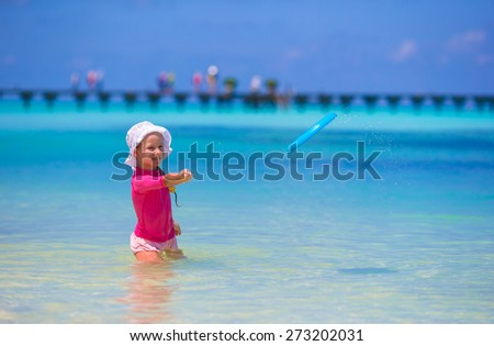Little girl playing with flying disc at wnite beach