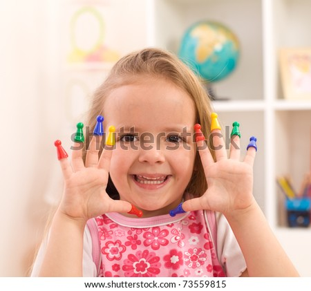 Little girl playing with game pieces fitting them on fingers