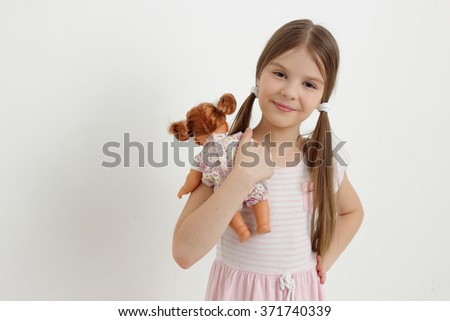 Little girl playing with her baby doll and pretending mom/Caucasian little girl and doll - stock photo