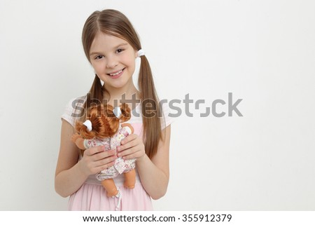 Little girl playing with her baby doll and pretending mom/little girl and doll - stock photo