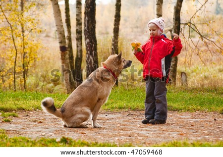 Little girl playing with her dog in autumn forest - stock photo