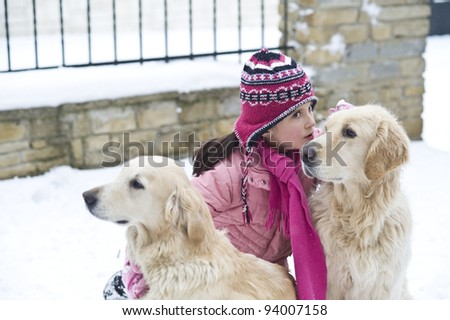 Little girl playing with her dogs