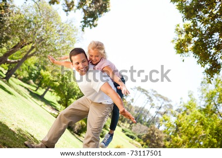 Little girl playing with her father in the park - stock photo