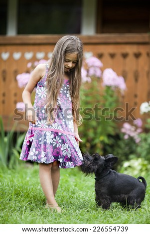 Little girl playing with her miniature schnauzer in backyard - stock photo