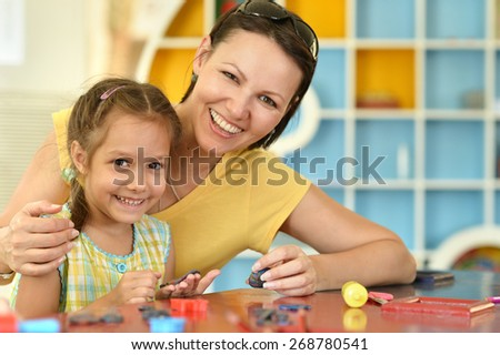 Little girl playing with her mother at home - stock photo