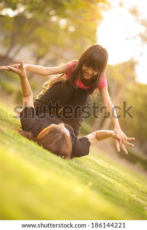 Little girl playing with her mother at outdoor - stock photo