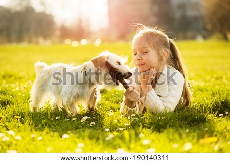Little girl playing with her puppy dog in the park - stock photo