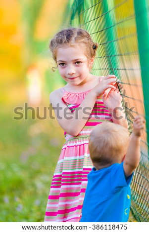 Little girl playing with her smaller brother outdoors. - stock photo