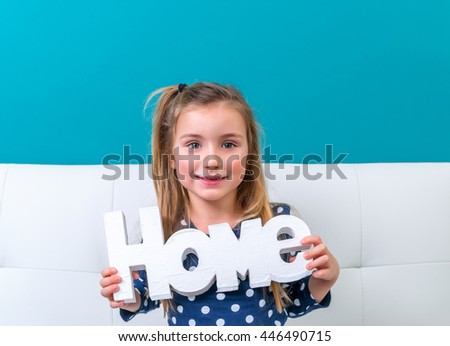 little girl playing with home letters on couch - stock photo